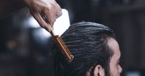 a man having his hair taken care of with a brush