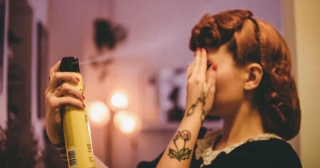 Women applying hairspray on her hair