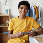 teenager with curly black hair in a yellow tshirt